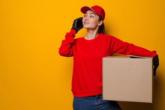 Junge asiatische lieferfrau, die box hält, die am telefon lokalisiert auf gelber wand spricht
