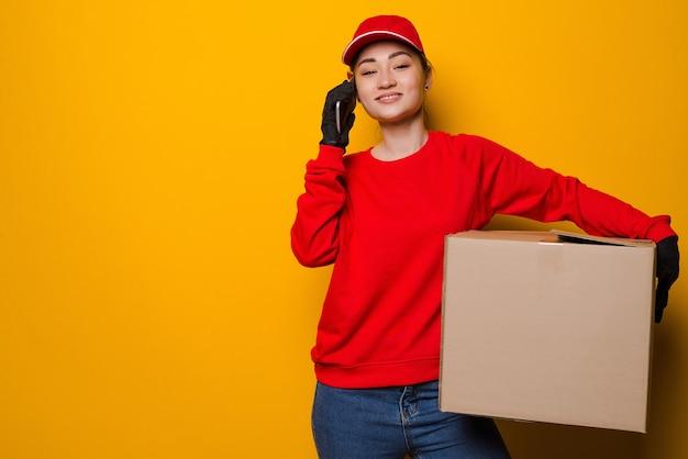 Junge asiatische lieferfrau, die box hält, die am telefon lokalisiert spricht