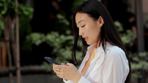 Junge asiatische mädchen, die die straße entlang gehen, während sie ihr smartphone benutzen und sich mit einem lächeln umschauen moderne geräte suchen nach sozialen online-netzwerken