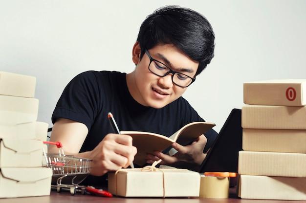 Junge asiatische männer casual style, entrepreneur schreiben sie detaillierte informationen zu lagerbeständen oder verpackungsboxen