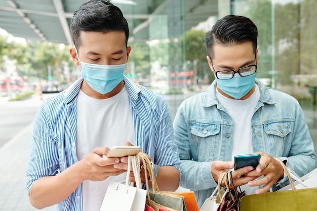 Junge asiatische männer in schutzmasken stehen auf der straße mit einkaufstüten und sms-freunden