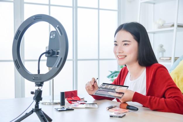 Junge asiatische make-up-künstlerin, beauty-vloggerin oder bloggerin, die kosmetische make-up-tutorial-vlog aufzeichnet