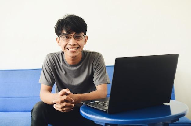 Junge asiatische mann sitzt sofa glückliches gesicht