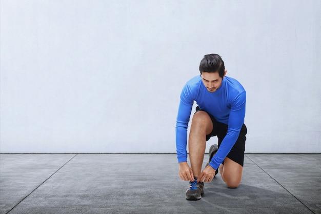 Junge asiatische mannbindungssport-schnürsenkel bevor dem laufen