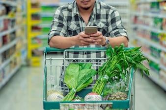 Junge asiatische Männer der Nahaufnahme, die den intelligenten Handy für Checkprodukt verwenden und die Laufkatze für s übergeben