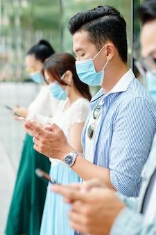 Junge asiatische menschen, die im freien in schutzmasken stehen und mobile anwendungen in ihren handys verwenden, um die coronavirus-statistiken zu überprüfen