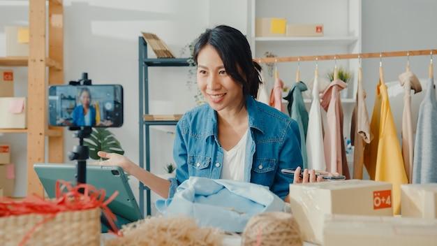 Junge asiatische modedesignerin, die das mobiltelefon verwendet, das bestellung erhält und kleidung im live-streaming zeigt