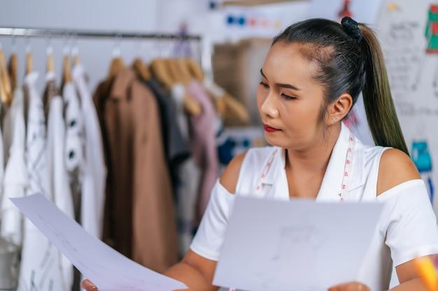 Junge asiatische modedesignerin oder schneiderin, die kleidungsskizze in der hand überprüft