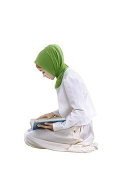 Junge asiatische moslemische frau, die den koran liest