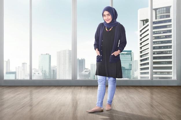 Junge asiatische moslemische frau mit der kopftuchaufstellung