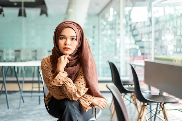Junge asiatische moslemische geschäftsfrau in der braunen hijab freizeitkleidung, die im kreativen café sitzt.