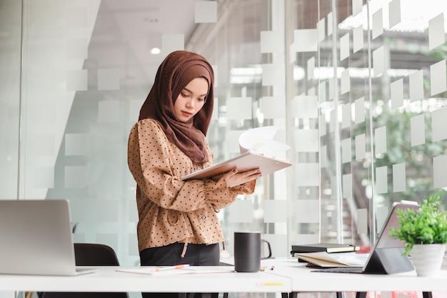 Junge asiatische moslemische geschäftsfrau in der braunen hijab freizeitkleidung geschäft besprechend und bei der stellung im kreativen café lächelnd.