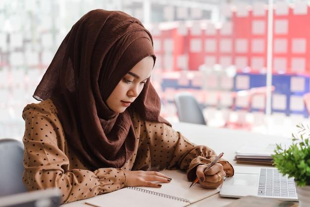 Junge asiatische moslemische geschäftsfrau in der intelligenten freizeitkleidung, im geschäft und im lächeln beim sitzen im kreativen coworking.