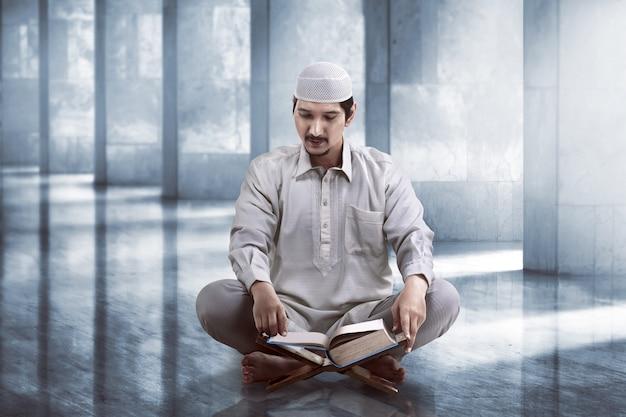 Junge asiatische moslemische leute, die koran lesen