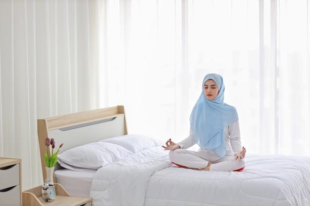 Junge asiatische muslimische frau, die auf bett sitzt und meditation genießt. schöne frau in nachtwäsche mit blauem hijab praktiziert yoga im schlafzimmer mit frieden und ruhe. gesundes und lifestyle-konzept