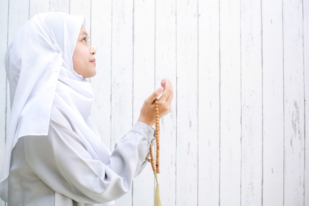 Junge asiatische muslimische frau, die das kopftuch trägt, das betet, während rosenkranzperlen mit kopienraum halten