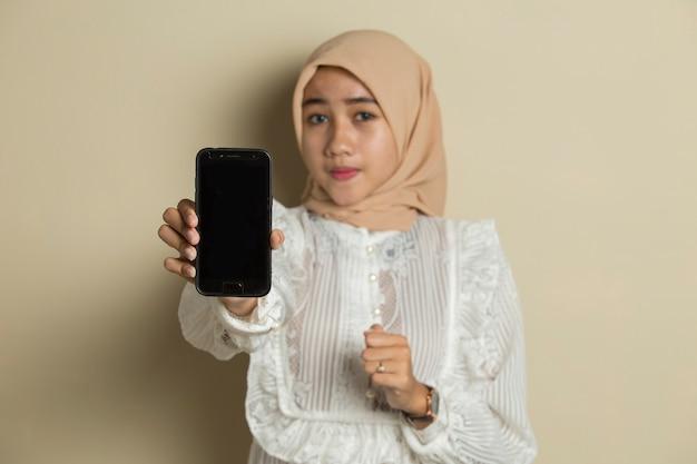 Junge asiatische muslimische frau, die hijab trägt und handy des leeren bildschirms zeigt