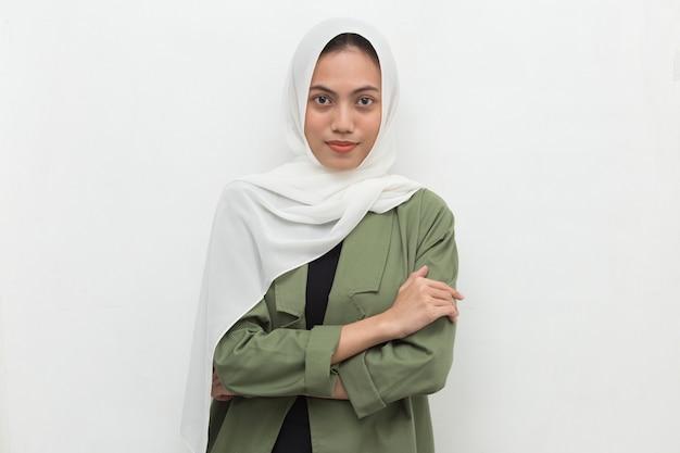 Junge asiatische muslimische frau im kopftuchlächeln mit verschränkten armen