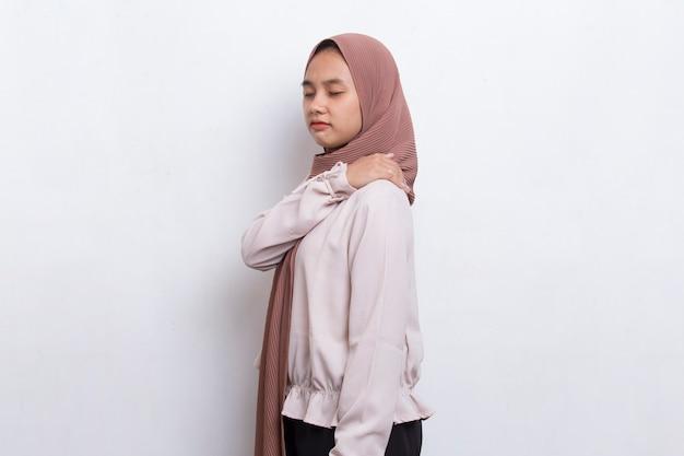 Junge asiatische muslimische frau mit hals- und schulterschmerzen und verletzungsmedizinischem konzept