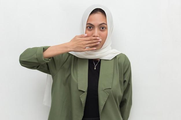 Junge asiatische muslimische frau schockiert, die mund mit händen für fehler geheimes konzept bedeckt