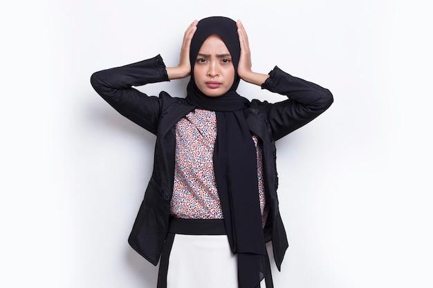Junge asiatische muslimische geschäftsfrau, die beide ohren mit den händen bedeckt, die auf weißem hintergrund lokalisiert werden