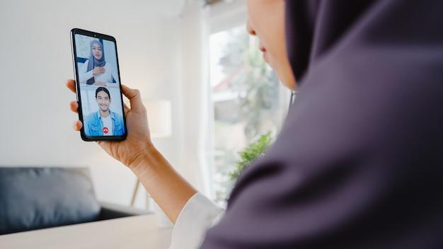 Junge asiatische muslimische geschäftsfrau, die smartphone verwendet, um per videochat mit kollegen zu sprechen?