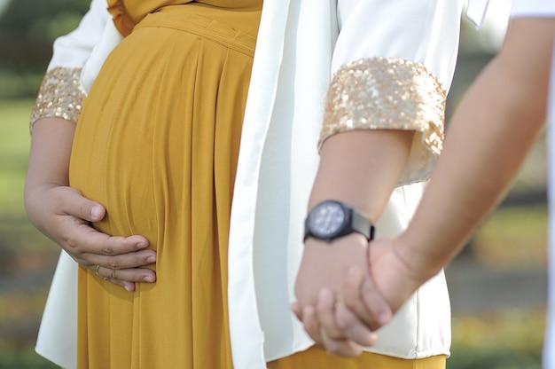 Junge asiatische muslimische paare, die schwanger gehen und die hände auf grünem gras hautnah zusammenhalten?