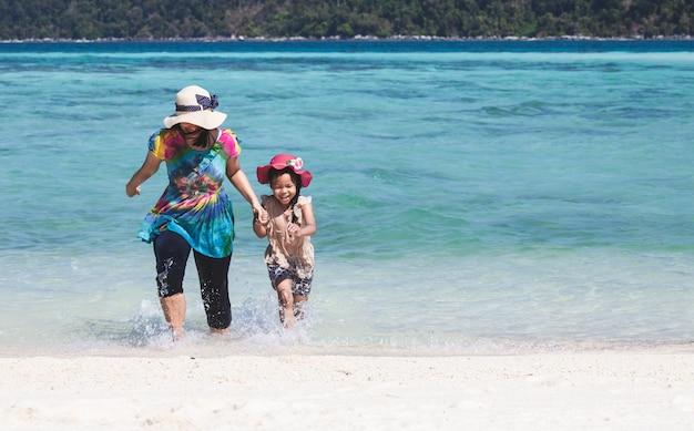 Junge asiatische mutter und nette kleine tochter, die zusammen wasser im schönen meer spielt