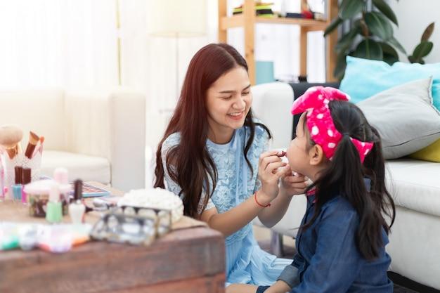 Junge asiatische mutter und tochter, die spaß zusammen mit make-upkosmetik habend spielt.