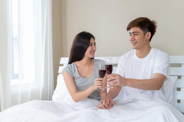 Junge asiatische paar füllen glücklich halten glas wein feiern im schlafzimmer