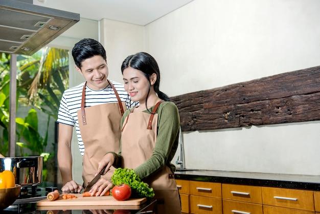 Junge asiatische paare, die auf der küche kochen