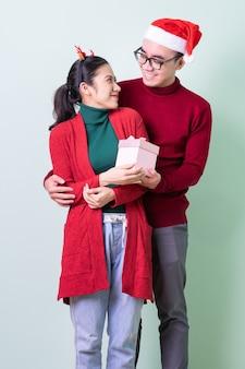 Junge asiatische paare, die auf grünem hintergrund mit weihnachtskonzept aufwerfen