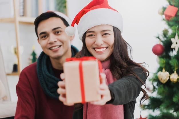 Junge asiatische paare, die eine geschenkbox während der weihnachts- und guten rutsch ins neue jahr zu hause hintergrund mit weihnachtsbaumdekoration für feiertagsfest geben. weihnachtsfeierkonzept.