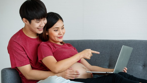 Junge asiatische paare, die entspannt zusammen auf einer couch sitzen. eine schwangere frau zeigt auf einen laptop-bildschirm, während ein mann lächelt und seine hände um sie legt. familienkonzept.