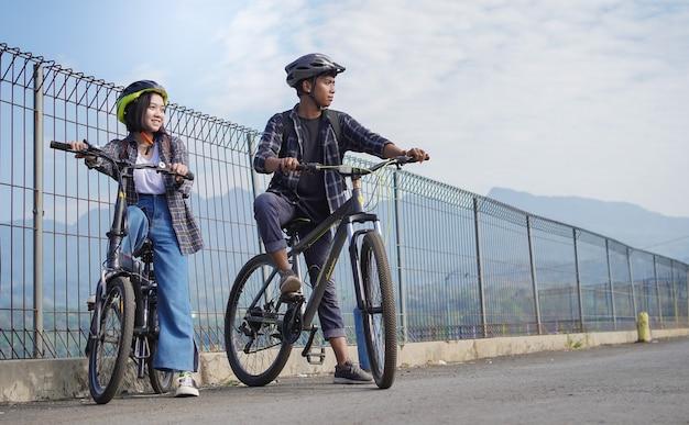 Junge asiatische paare, die sich nach der fahrt mit dem fahrrad ausruhen, gehen zur arbeit