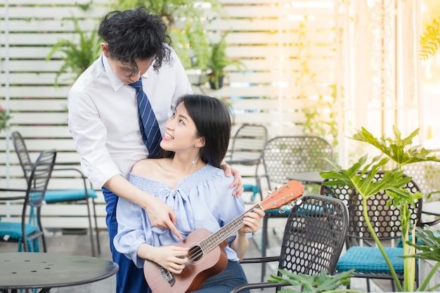 Junge asiatische paare in der liebe, die gitarre, glückliches mischrassejugendlichkonzept spielt