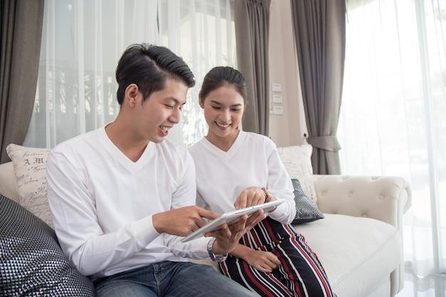 Junge asiatische paare unter verwendung der digitalen tablette auf sofa zu hause.