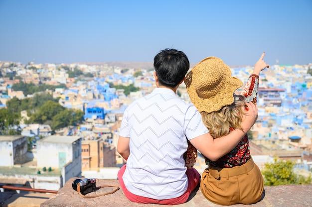 Junge asiatische paarreisende sitzen genießen ansicht der blauen stadt von jodhpur in rajasthan, indien