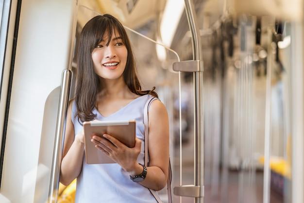 Junge asiatische passagierin, die soziales netzwerk über technologietablett in der u-bahn nutzt