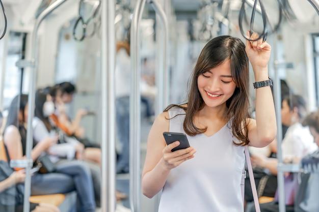 Junge asiatische passagierin mit sozialem netzwerk über smartphone in der u-bahn
