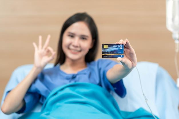 Junge asiatische patientin, die mock-up-gesundheitskreditkarte hält