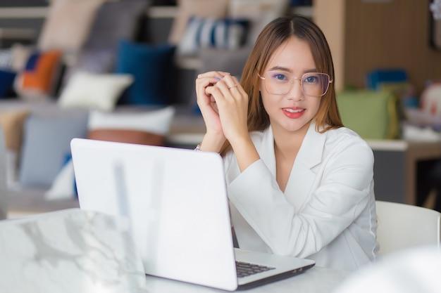 Junge asiatische professionelle geschäftsfrau mit brille arbeitet im co-working-raum mit laptop-papierkram (geschäftsfrauenkonzept).