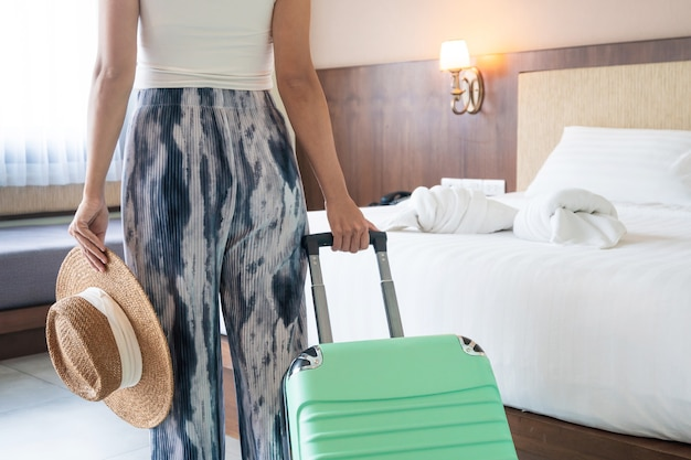 Junge asiatische reisende frau mit grünem gepäck und strohhut im hotelzimmer nach dem einchecken