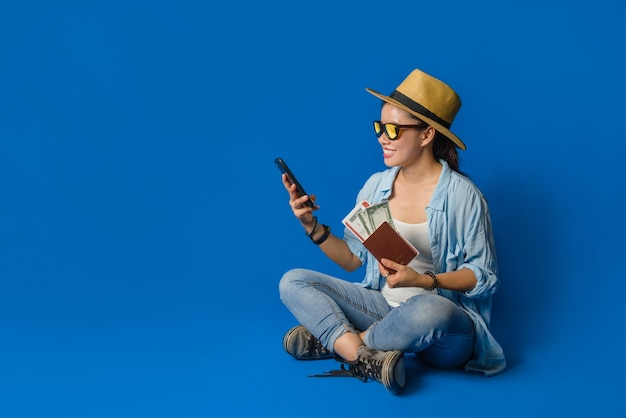 Junge asiatische reisende glücklich im blauen hemd mit reisepass mit mobiltelefonen in der hand. konzeptreisen mit ausrüstung für reisende urlaub, auf blauem hintergrund. reisen entspannen