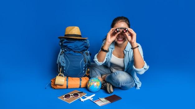 Junge asiatische reisende glückliche frau im blauen hemd mit rucksack mit und ausrüstung für reisende urlaub mit einer karte, auf blauem farbhintergrund. reiserucksack