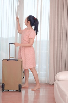 Junge asiatische reisende in rosa kleid mit ihrem gepäck kommt im hotelzimmer und offenem vorhang an, um eine außenansicht zu genießen, glücklicher frauenlebensstil mit urlaubskonzept für sommerreisen