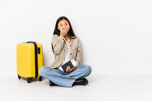 Junge asiatische reisendfrau, die eine bordkarte durchdacht halten und mund mit der hand bedecken sitzt