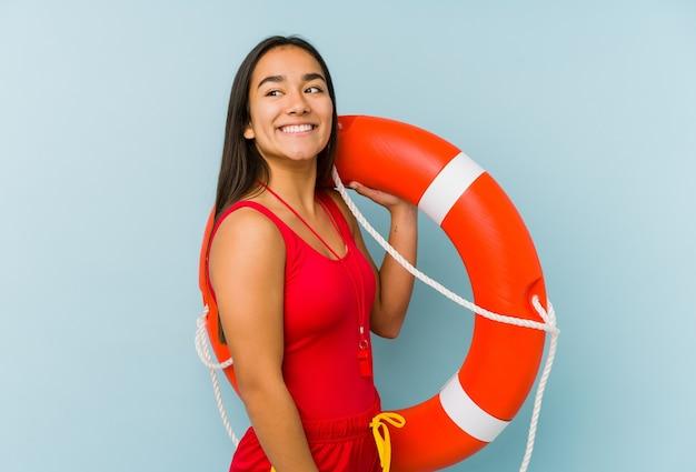 Junge asiatische rettungsschwimmerin isoliert sieht lächelnd, fröhlich und angenehm beiseite