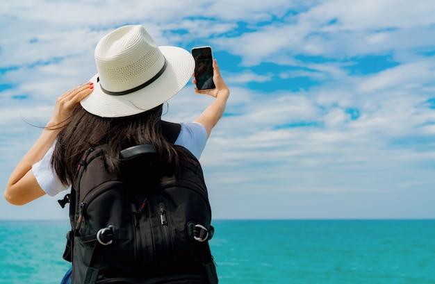 Junge asiatische rucksacktouristin tragen hut verwenden smartphone, das selfie am pier nimmt. sommerferien am tropischen paradiesstrand. frau genießen und entspannen das leben. sommergefühl.