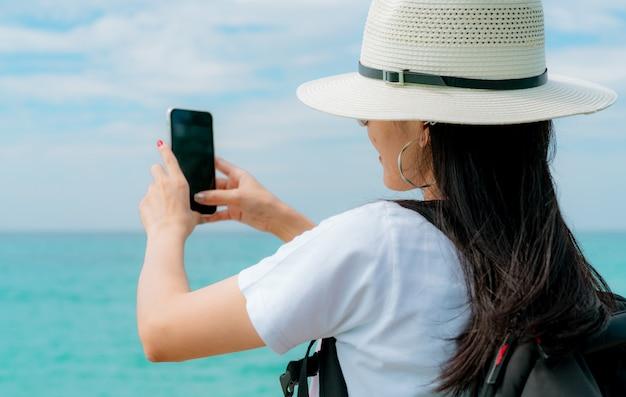 Junge asiatische rucksacktouristin tragen hut verwenden smartphone, das selfie am pier nimmt. sommerferien am tropischen paradiesstrand. glückliches hipster-mädchen reisen im urlaub. sommergefühl.